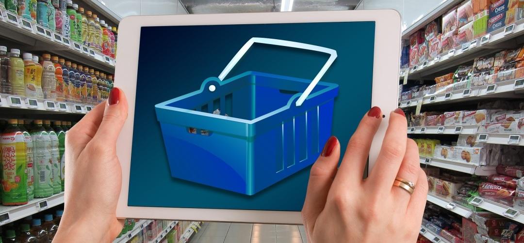 Una mujer tiene una tablet con una imagen de cesta y está en un supermercado marcas comerciales consumismo